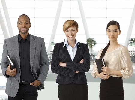 Interraciale team van ondernemers staan voor portret in het bedrijfsleven hal, glimlachend. Stockfoto