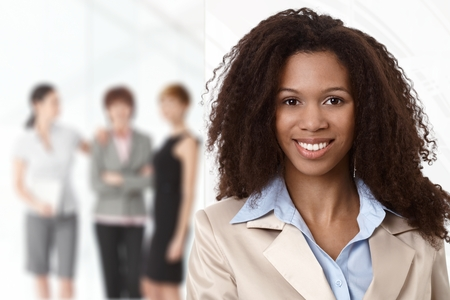 Portrait of afro businesswoman at office, colleagues in background. Stock Photo