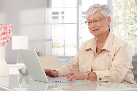 Elderly woman sitting at home, using laptop computer, smiling.