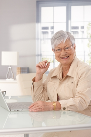 Mature woman sitting at home, using laptop computer, smiling happy. photo