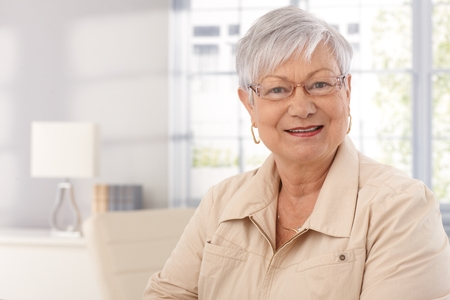 Closeup portrait of mature woman at home, smiling, looking at camera. Stock Photo