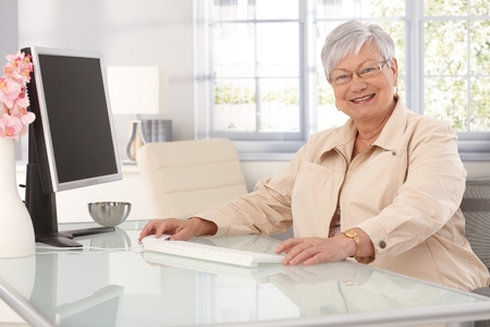 Happy elderly lady sitting at table at home, using computer, smiling at camera. photo