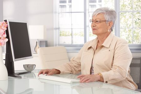 Mature woman sitting at table at home, using computer. photo