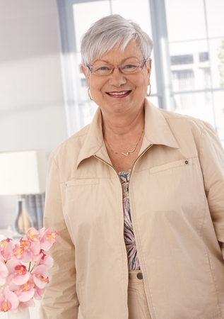 Portrait of happy smiling elderly lady, looking at camera. Stock Photo