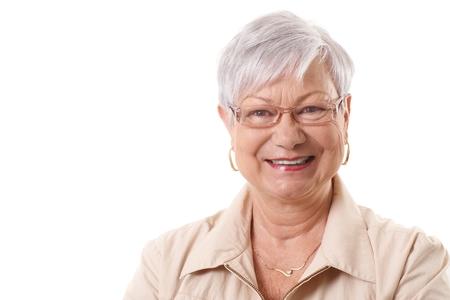 Close-up portret van gelukkig lachende oudere dame, kijkend naar de camera.