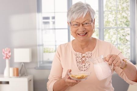 Happy elderly lady preparing breakfast cereal, pouring milk, looking at camera.