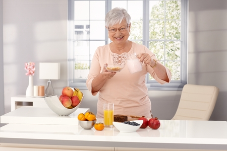 Happy old woman preparing healthy breakfast, pouring milk over cereals, smiling, looking at camera.