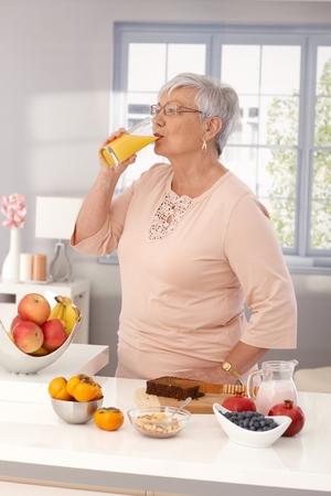Elderly woman drinking orange juice, preparing healthy breakfast with brown bread and fruits.