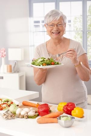 Avó moderna comer salada verde e legumes frescos na cozinha, sorrindo feliz, olhando a câmera.