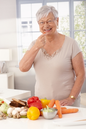 Happy grandmother standing in kitchen using fresh raw materials to prepare healthy food. photo