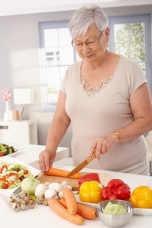 Old lady preparing healthy food from fresh vegetables in kitchen, slicing carrots.