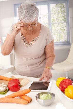 Contemporary old lady using tablet in kitchen to prepare healthy meal. photo