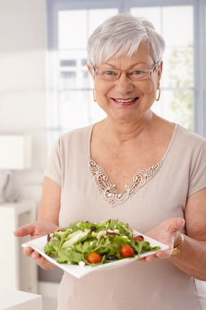Happy old lady holding plate of fresh green salad, looking at camera.