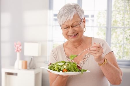 eten: Gelukkige oude dame het eten van verse groene salade, glimlachend.