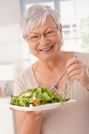 Happy old woman eating fresh green salad, smiling, looking at camera.