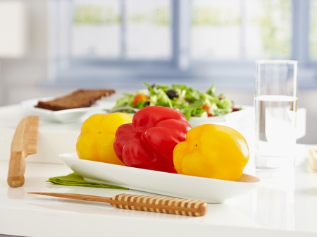 low calorie: Healthy, low calorie food on tabletop, plate of sweet peppers, salad and brown bread.