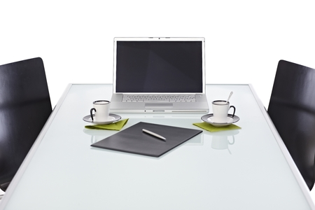 opaque: Office desk with silver laptop on opaque glass office desk, chairs, coffee cup, clipboard and pen, ready for business meeting. Blank screen, white background. Stock Photo