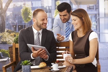 Happy caucasian business team having an outdoor meeting at restaurant using tablet computer. Imagens