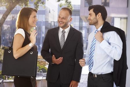 Homem de negócios feliz que introduz novo parceiro para atraente colega, ao ar livre. Terno e gravata. Imagens