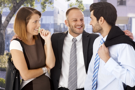 overly: Overly happy, annoying businessmen celebrating with startled female colleague after work, outdoors. Stock Photo