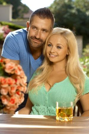 tetona: Retrato de la joven pareja romántica sentado en el jardín de verano, al aire libre. Mujer atractiva, rubia tetona con escote.