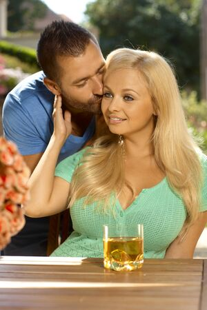 be kissed: Portrait of romantic young couple kissing at summer garden, outdoors. Attractive, busty blonde woman with cleavage.