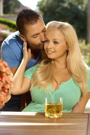 be kissed: Ritratto di giovane coppia romantica baciare in giardino estivo, all'aperto. Attraente, donna bionda procace con fenditura.