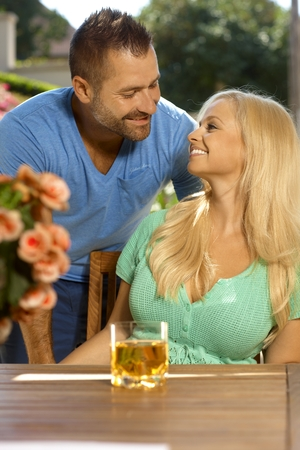 busty woman: Portrait of romantic young married couple, summer, outdoors. Attractive, busty blonde woman with cleavage. Looking at each other. Stock Photo