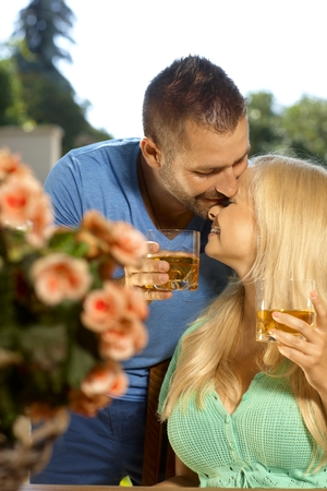 be kissed: Portrait of romantic young couple kissing with drinks in hand, outdoors. Attractive, busty blonde woman with cleavage. Stock Photo