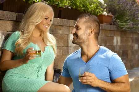 busty woman: Romantic young couple with drinks in the garden, glasses of whiskey, looking at each other, smiling.
