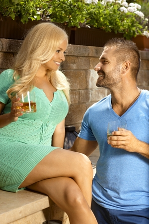 ladies bust: Romantic young couple dating outdoors with drinks in hand, looking at each other, smiling.