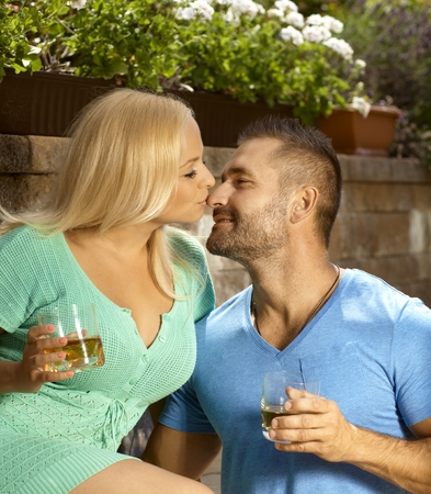 be kissed: Romantic young couple with drinks in the garden, glasses of whiskey, kissing, smiling. Stock Photo
