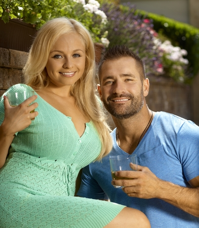 busty woman: Romantic young couple dating outdoors with drinks in hand, looking at camera, smiling.