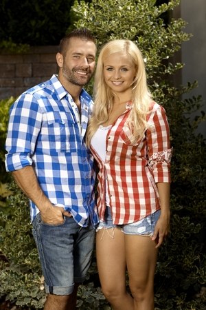 stubbly: Portrait of happy married couple outdoors, with attractive blonde, smiling woman and stubbly handsome man, wearing checkered shirt, shorts, looking at camera. Stock Photo