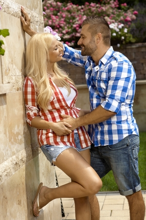 Confident casual handsome man dating young blonde girl outdoors, smiling, leaning against wall. photo