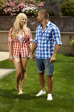 vertical garden: Happy casual married couple in outdoor garden, smiling. Attractive blonde woman and handsome man in shorts. Full size. Stock Photo