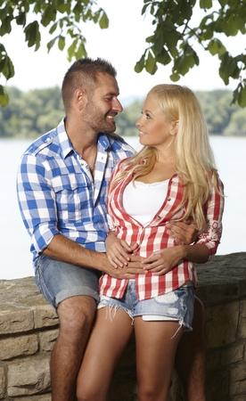 hombre romantico: Hombre rom�ntico ocasional feliz abrazar la joven mujer rubia al aire libre, sonriendo, mirando el uno al otro.
