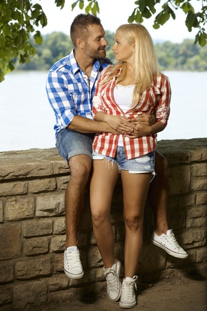 sport shoe: Happy romantic couple embracing at riverside, looking at each other, outdoor, full length, shorts, sport shoe. Stock Photo