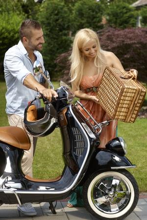 casco moto: Feliz pareja caucásico ir para la comida campestre al aire libre con elegante scooter. Atractiva mujer rubia sonriendo, canasta. Foto de archivo