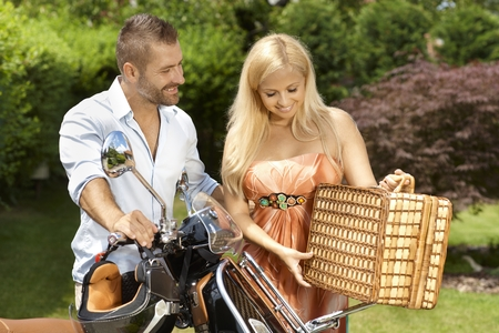 Happy casual caucasian couple with scooter and picnic basket. Blonde smiling woman with handsome man, outdoor. photo