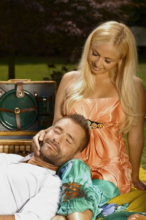 Relaxed smiling casual man laying in lap of happy romantic blonde woman at picnic, outdoor. photo