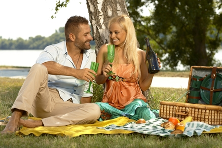 Young happy caucasian casual couple drinking champagne sitting at picnic. Handsome man and attractive woman smiling, romance, outdoor. photo
