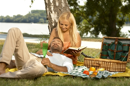 on lap: Casual handsome man sleeping at picnic in lap of attractive blonde girlfriend reading a book. Smiling, outdoor, basket. Stock Photo