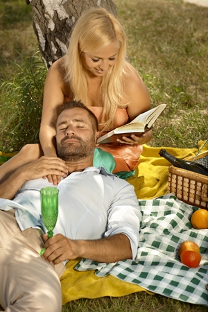 Happy blonde casual attractive woman reading for resting, handsome man after picnic. Smiling, high angle, outdoor. photo