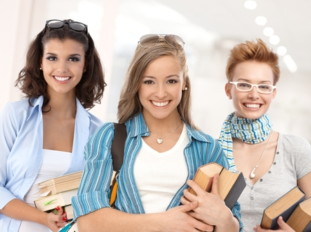 Group of happy student girls on school corridor looking at camera, smiling. Stock Photo - 26250707