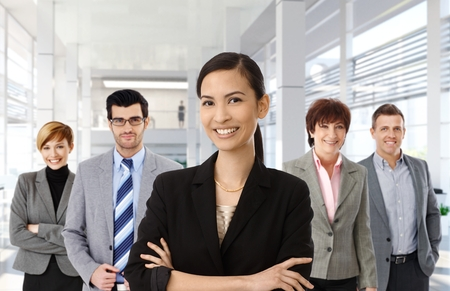 asian american: Happy asian businesswoman leading team of business people.