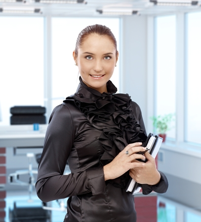 executive office: Portrait of elegant young female secretary at executive office, smiling. Stock Photo