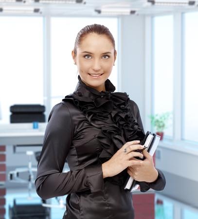 ejecutivo en oficina: Retrato de elegante joven secretaria en la oficina ejecutiva, sonriendo.