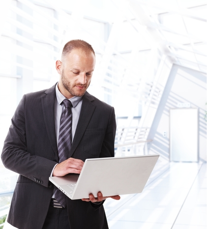 bristly: Caucasian businessman standing at office working with laptop computer.