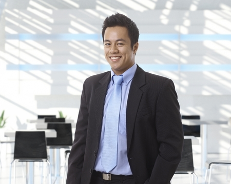 Portrait of happy asian businessman at office lobby, smiling. photo